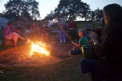 People sitting around a campfire at dusk