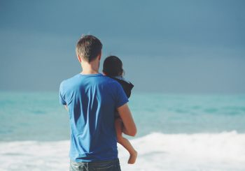 parent holding child at the beach